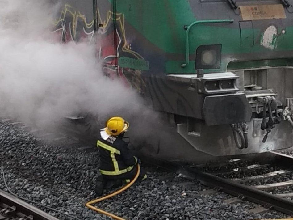 Un bombero junto a la máquina del tren